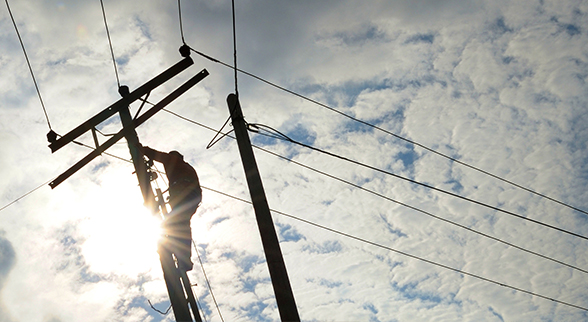 Image of a Lineman on an electrical pole doing work