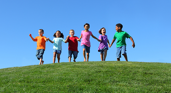 Image of Young Children Running Down a Grassy Hill