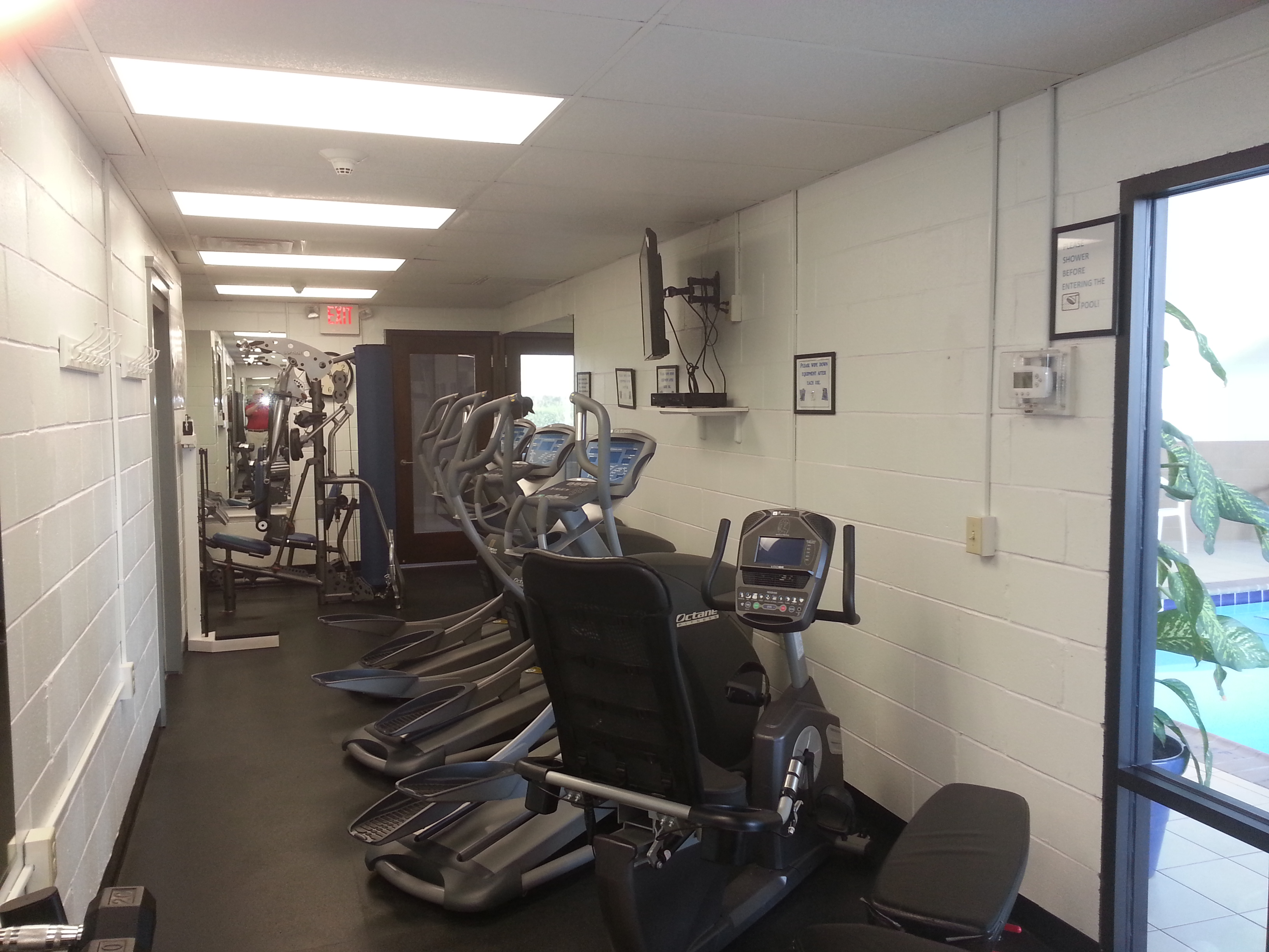 On the ground level next to the indoor pool is a clean, well lit fitness room.