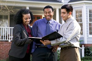 Realtor with Couple in Front of House