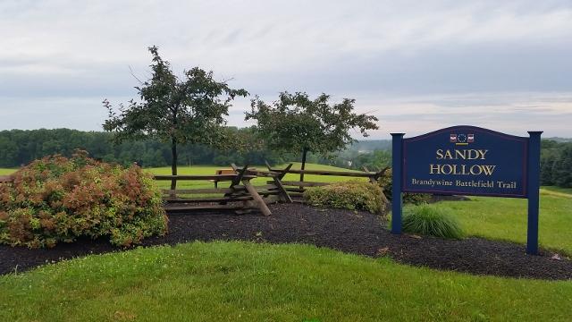 Sandy Hollow Brandywine Battlefield Trail sign next to large green field near The Knolls of Birmingham.
