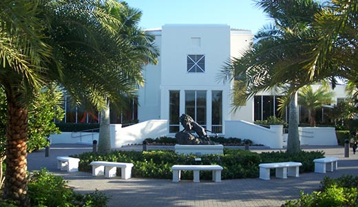 Entrance to Vero Beach Museum of Art featuring large bronze statue of mature male lion standing on rocks