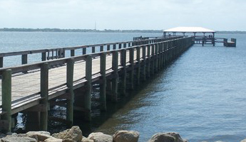 Long pier over dark river and large rocks