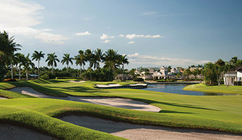 Luxury golf course in Florida with lush greens, sand traps and large water feature surrounded by luxury homes and tall palm trees