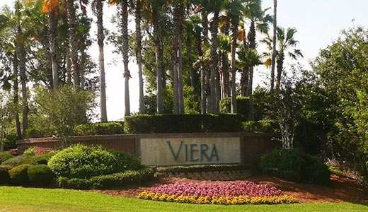 Entrance to the Viera community with manicured lawn, pink and yellow flowers, multiple palm trees and other bushes and shrubs. Sign reads Viera in blue letters with a cream tile background layered on red brick
