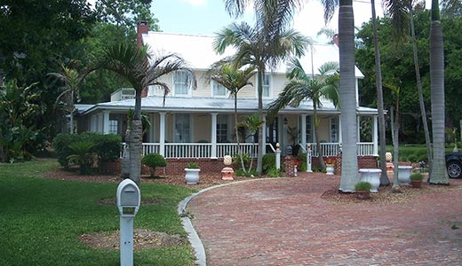 A historic Florida plantation home with white window panes and a covered walk-around porch surrounded by palm trees and a red brick driveway