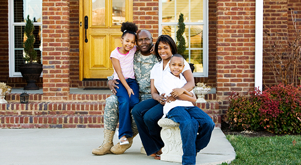 Image of Serviceman with Wife, Daughter and Son in front of their home