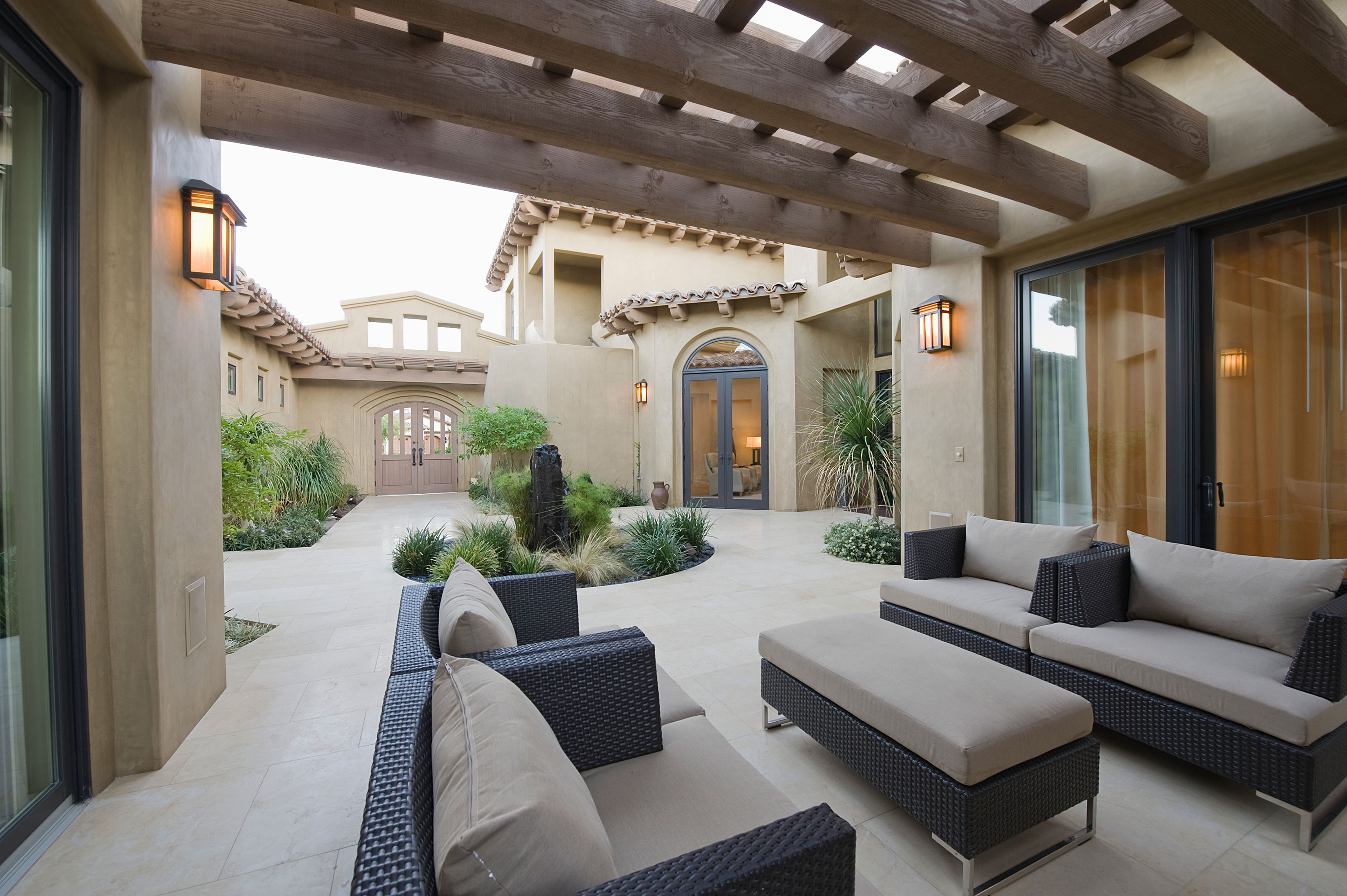 Outdoor seating in courtyard of home with wood beams overhead