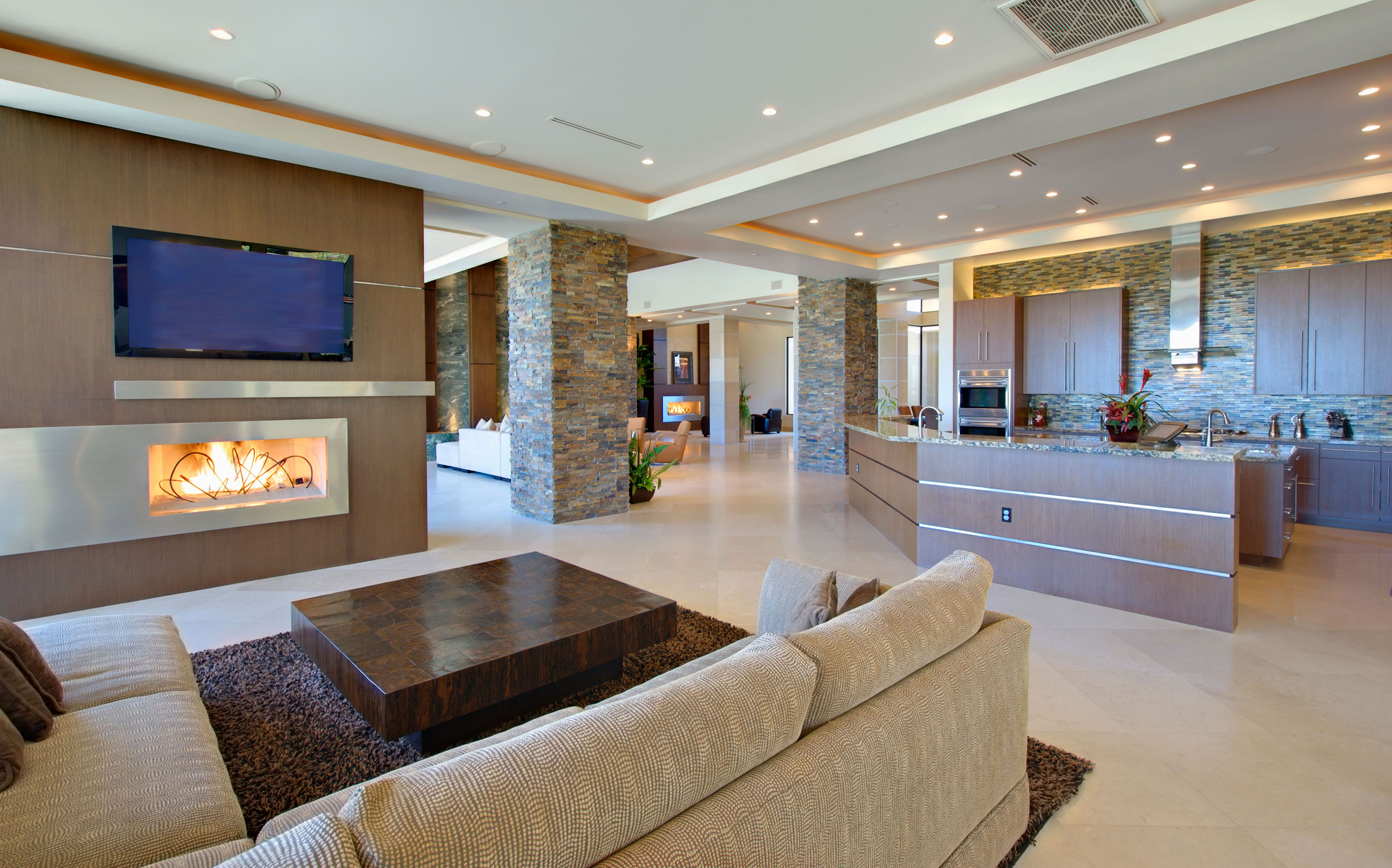 Neutral and brown seating area with electric fireplace near kitchen with multiple seating areas in distance