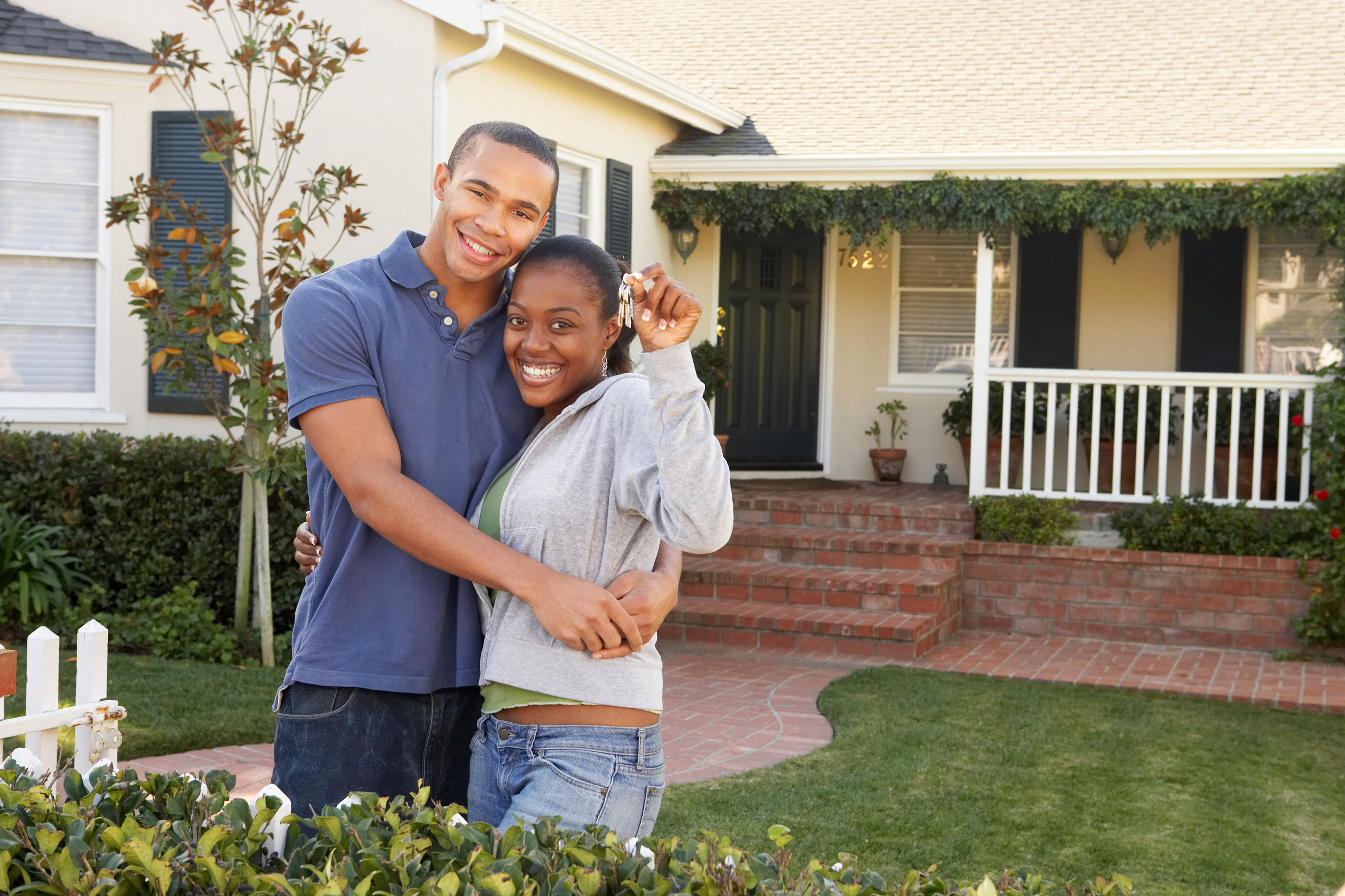 Man and woman smiling in front of home with brick steps holding keys
