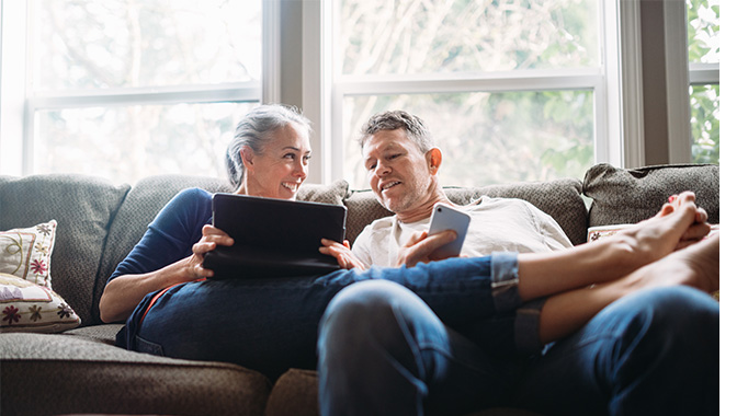 Older man and woman laying on sofa looking at a mobile phone and tablet