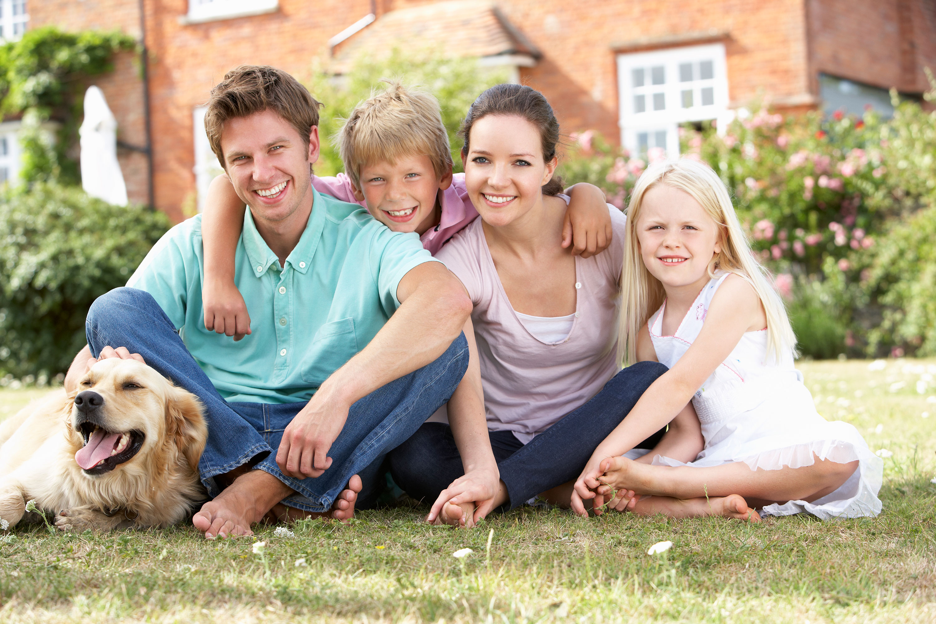 Family of four smiling with dog sitting on the grass in front of brick home