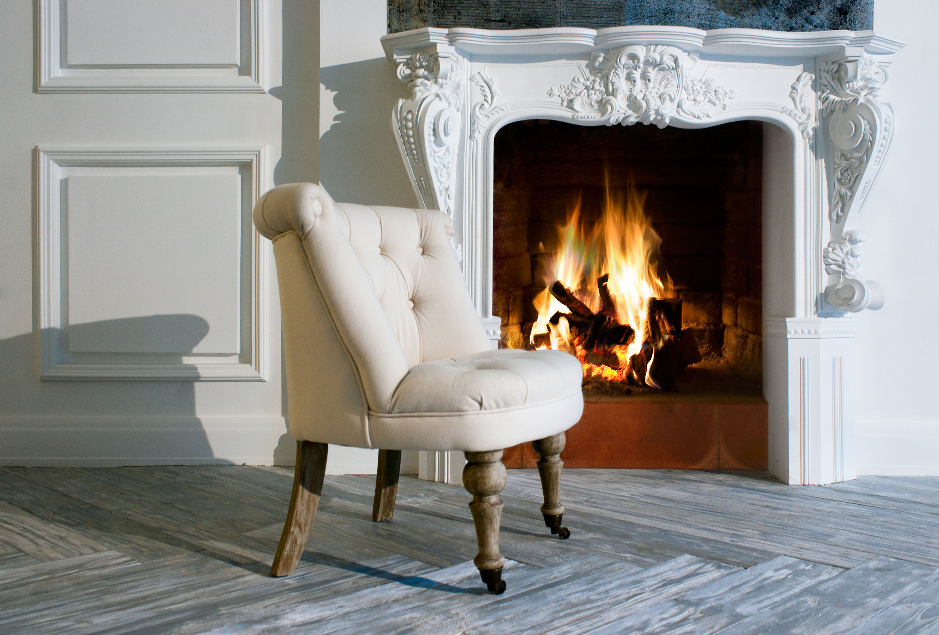 Cream chair in front of fireplace with white scrolled mantle and white walls