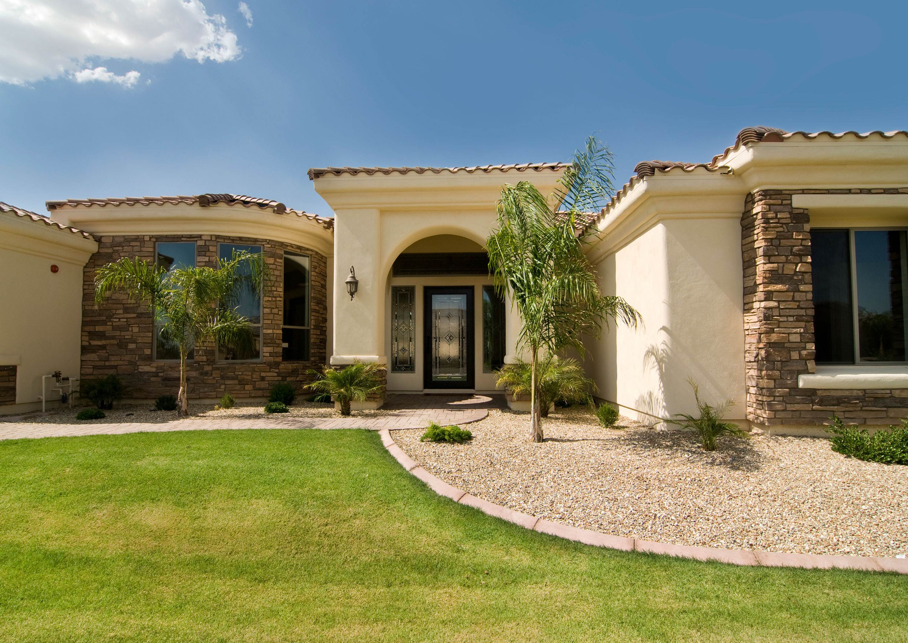 Exterior of tan and stone home with ceramic tile roof and etched glass front door with grass palms and rock