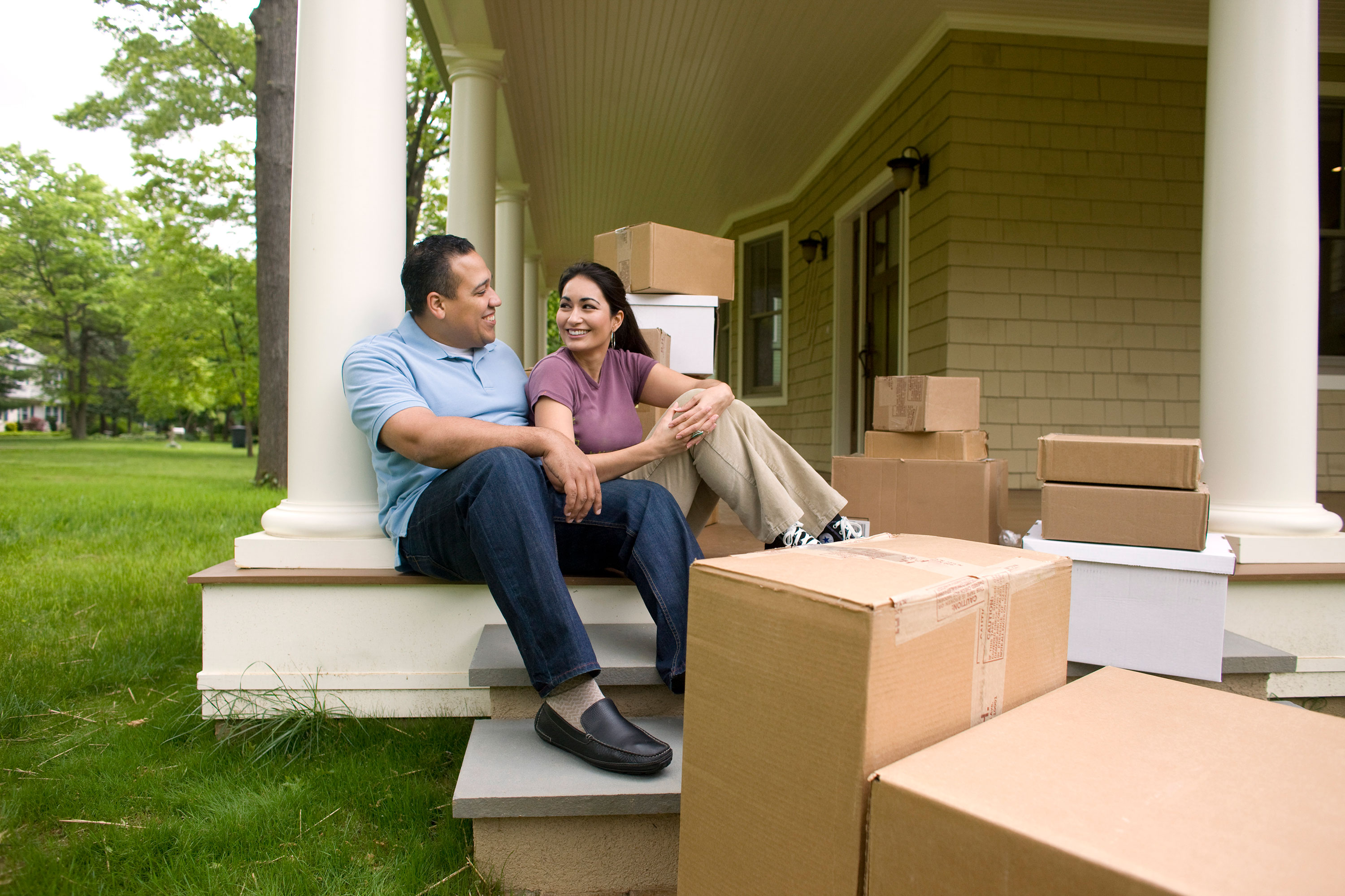 Man and woman sitting on porch with cardboard boxes