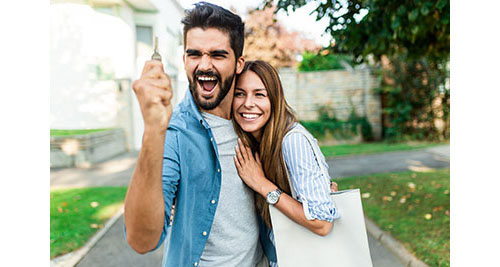 young couple with house keys smiling