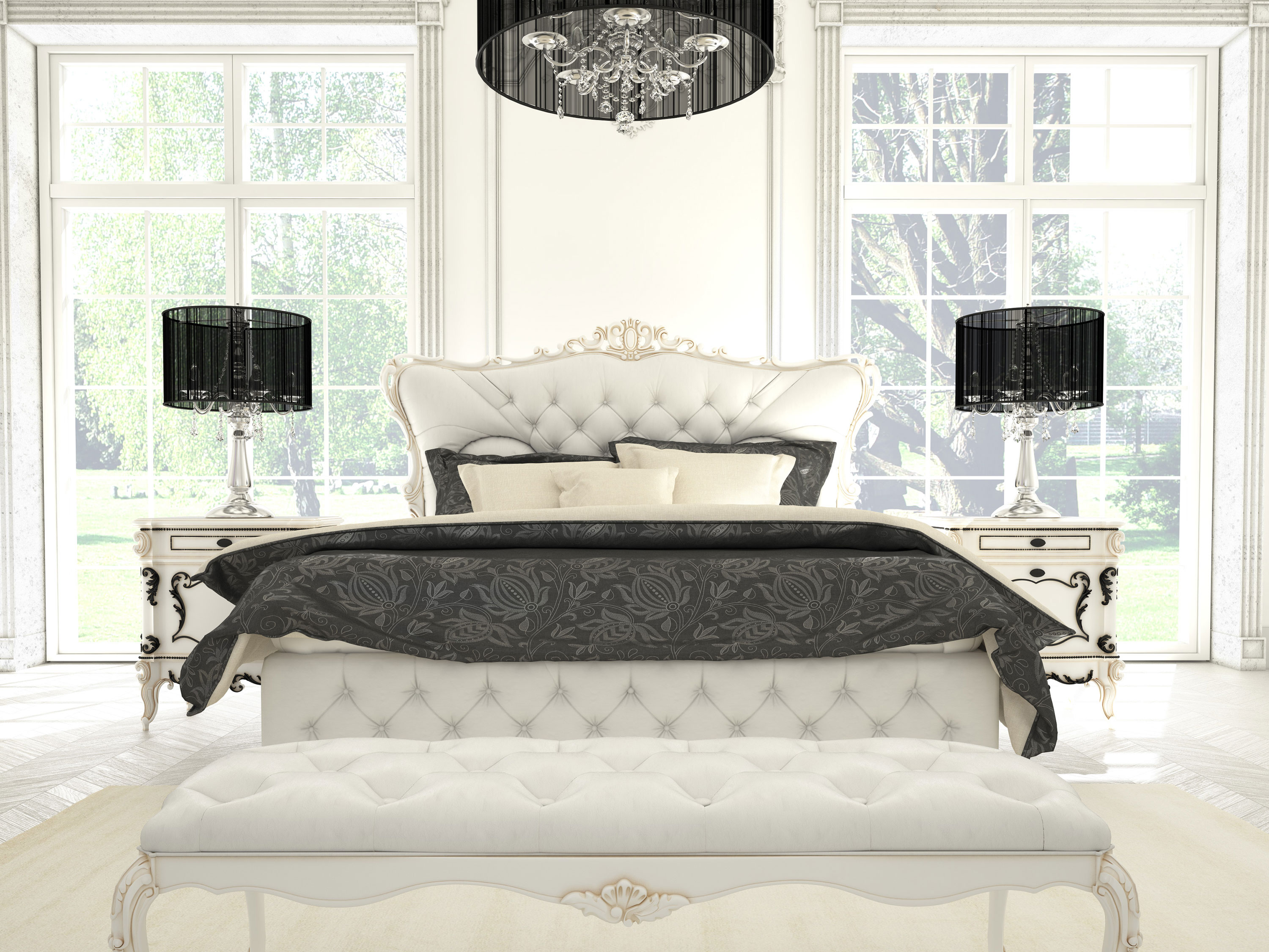 Bed with white tufted head and footboard with black fixtures and duvet in white room