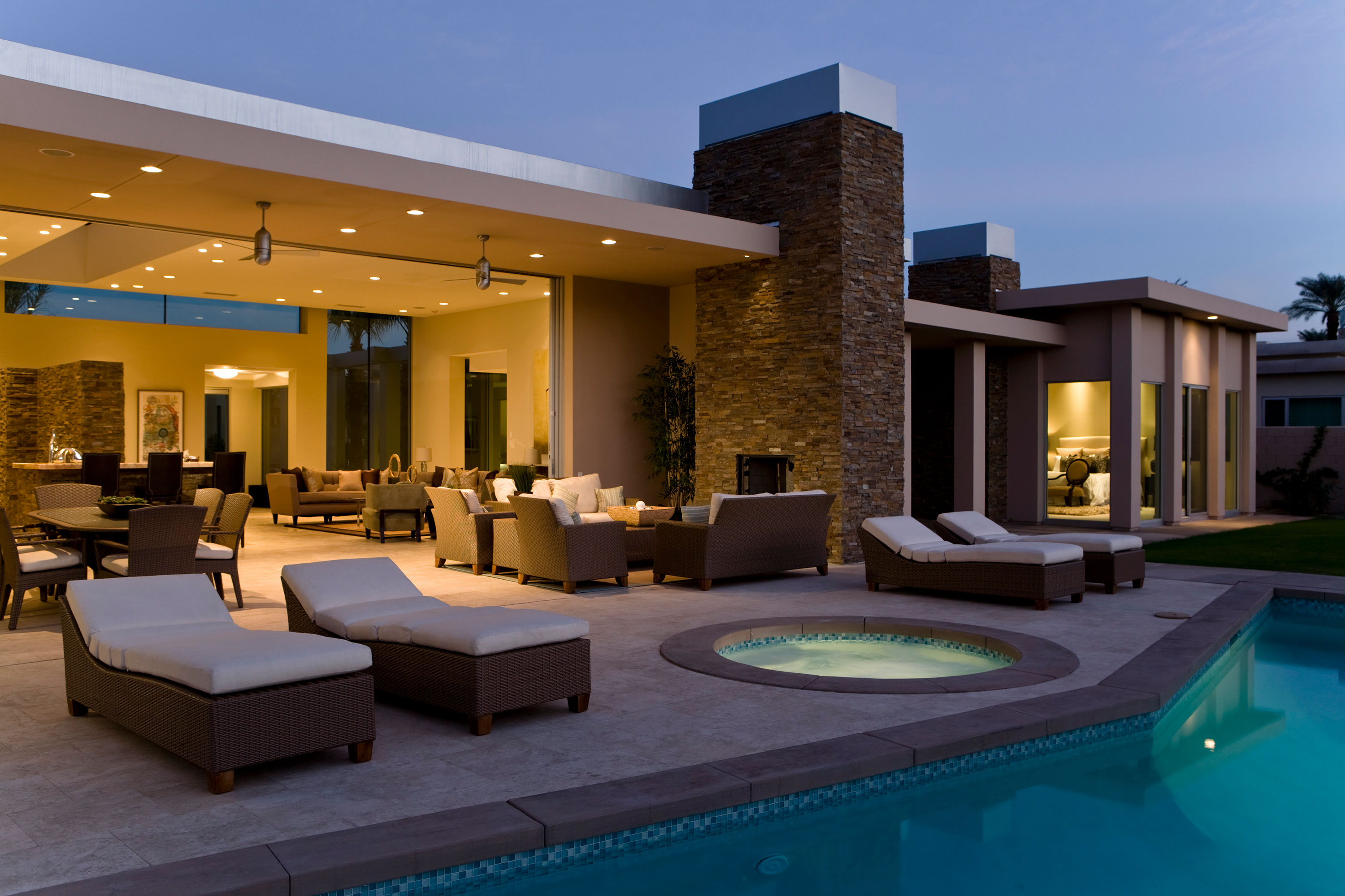 Outdoor seating area next to pool and jacuzzi with opening into home