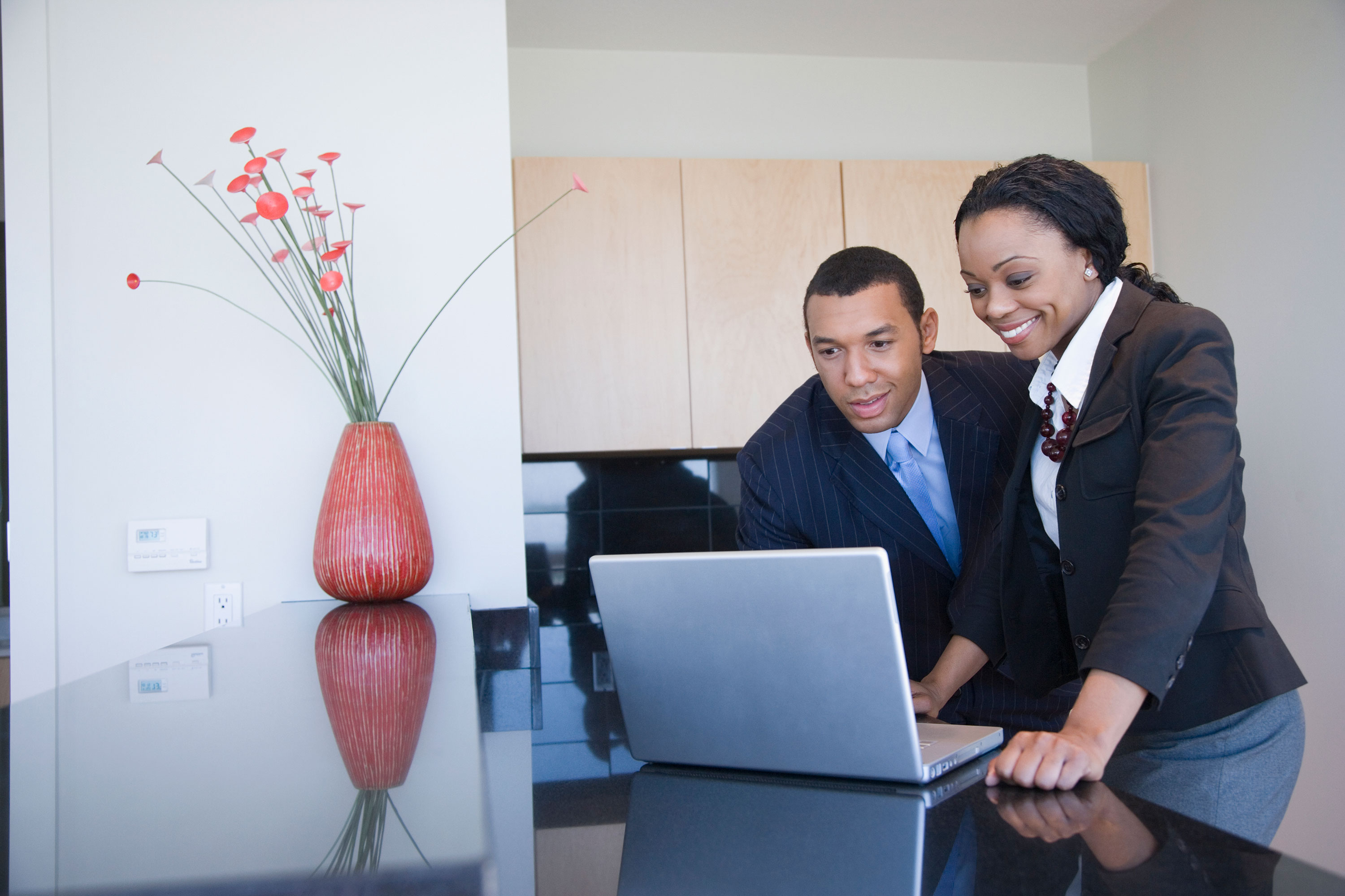 Man and woman standing and smiling at a laptop with a coral vase with coral stems on a black table