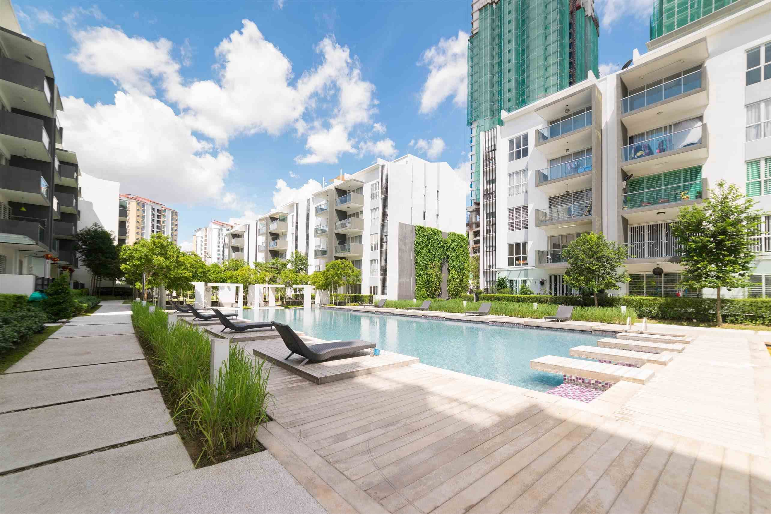 Pool area between apartment buildings with gray lounge chairs