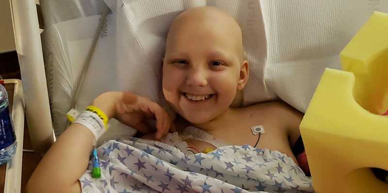 alexis-black child cancer smiling hospital bed chemo