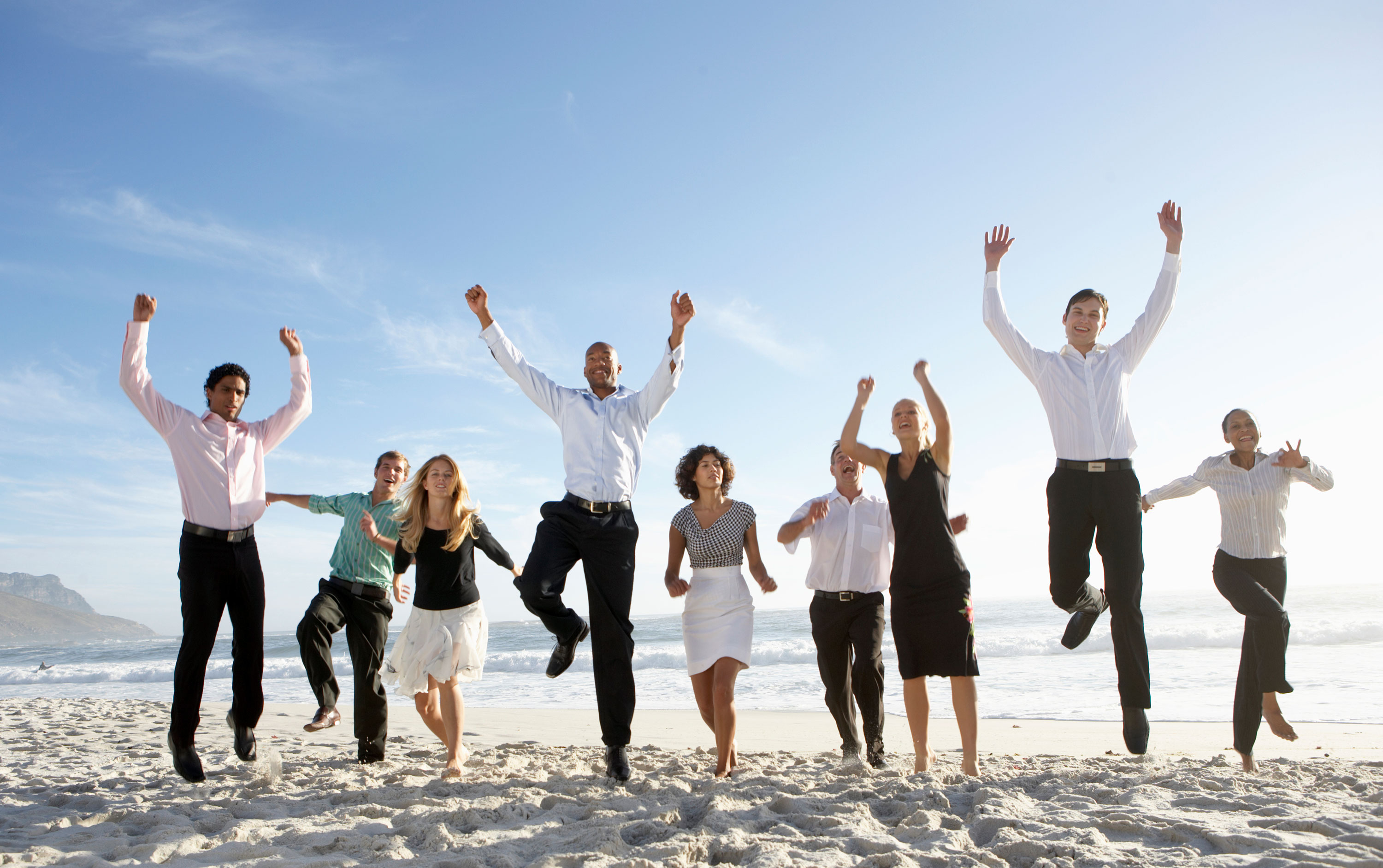 Nine people in clothes with some jumping up on the beach