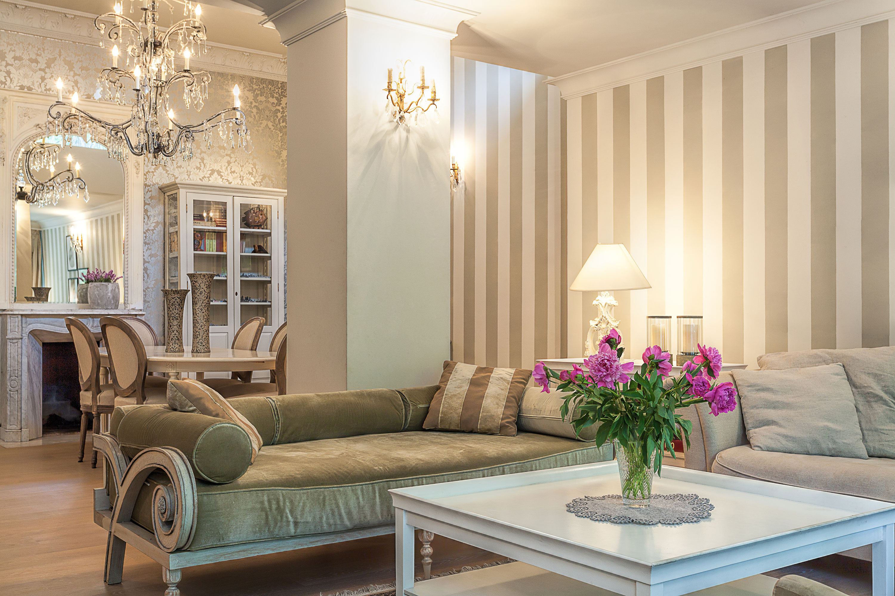 Formal area with low sofa beige and cream wallpaper with pink flowers in vase on white table