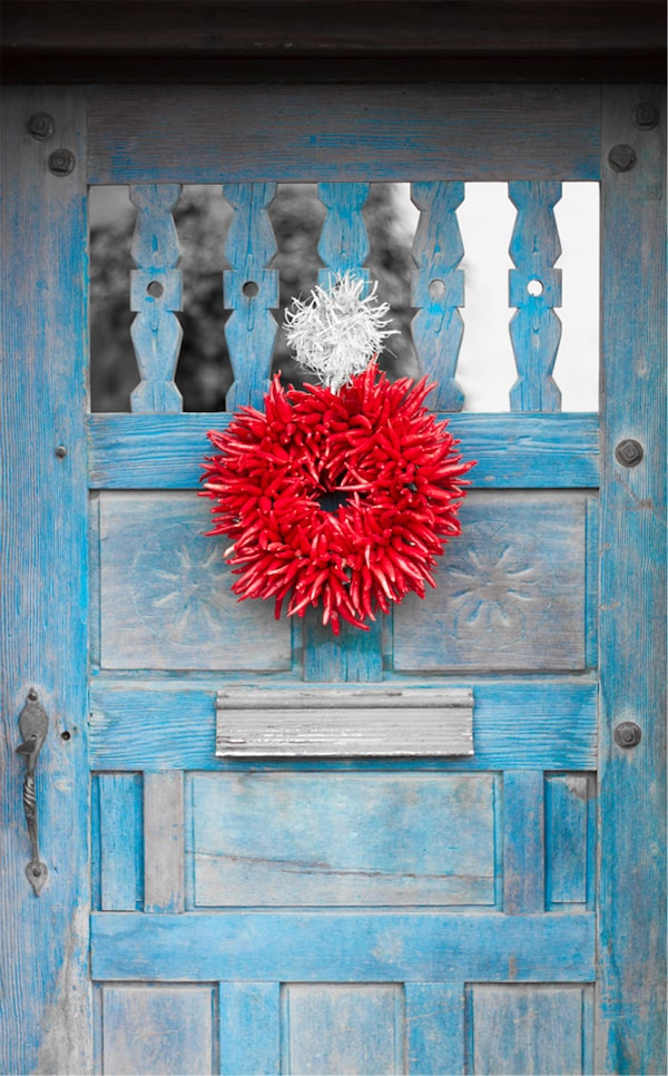 Exterior view of rustic front door made of weathered wood painted blue and a wreath of chili peppers.