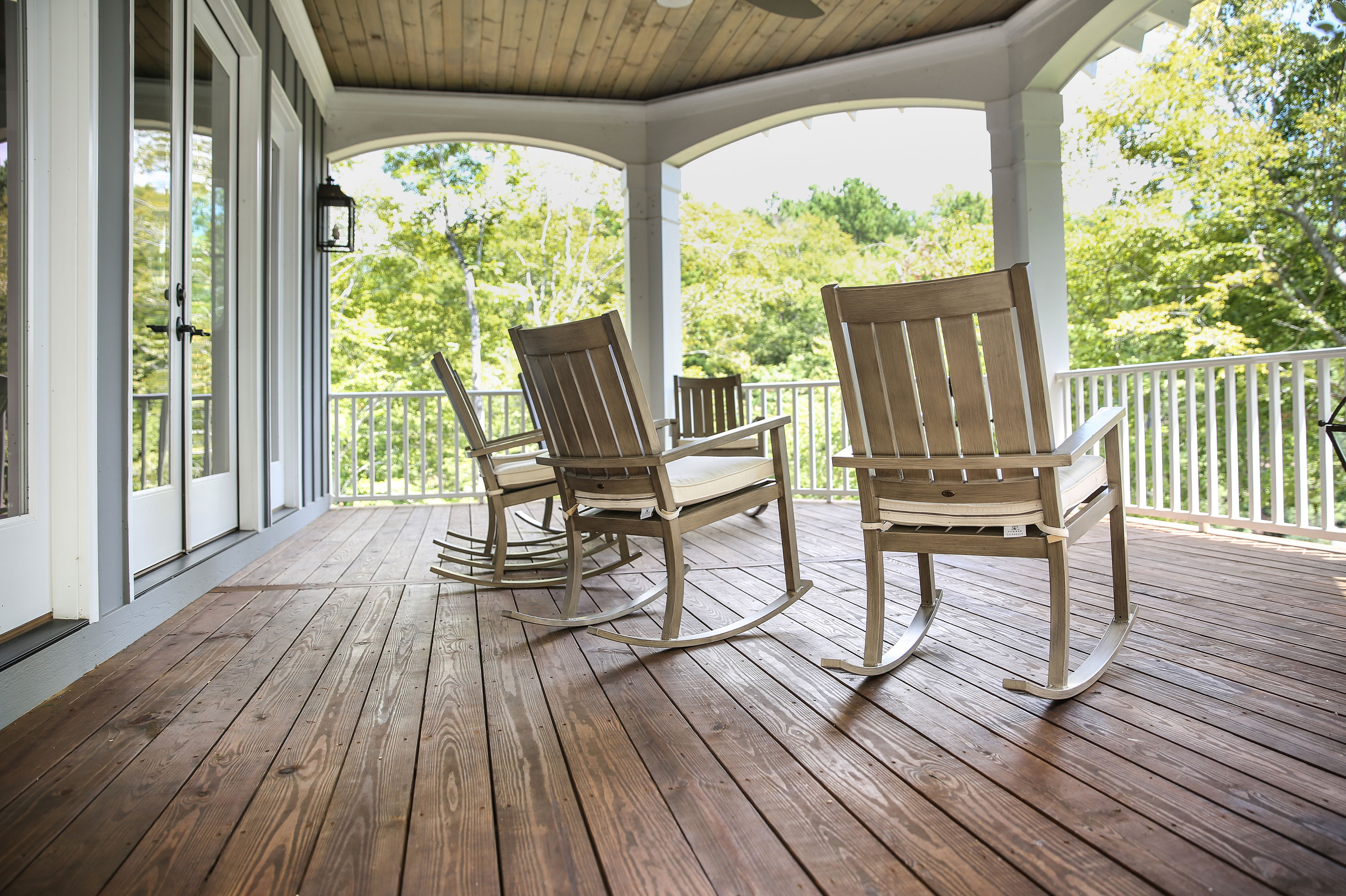 White and wood balcony with six light wood rocking chairs