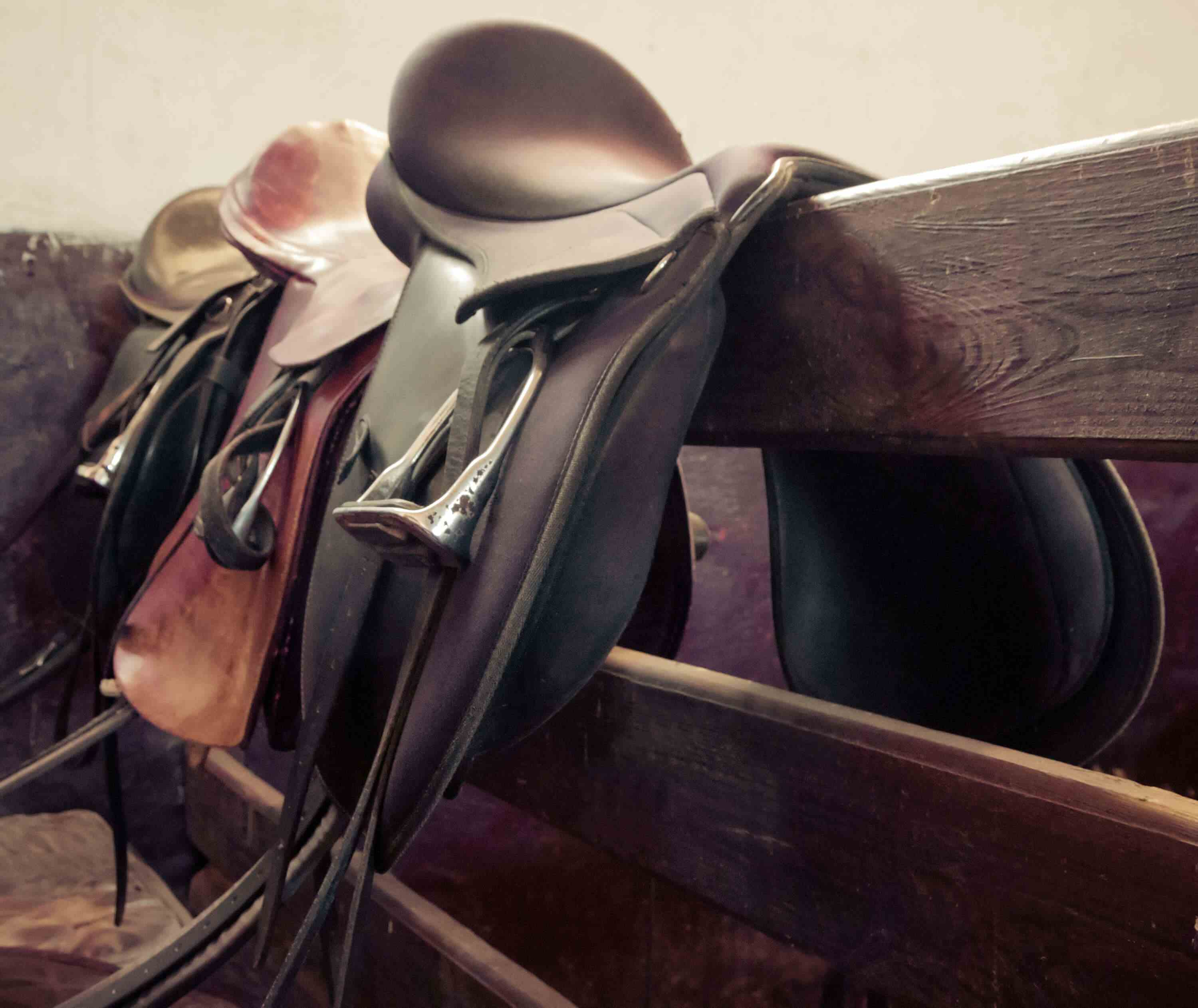 Saddles over a brown railing