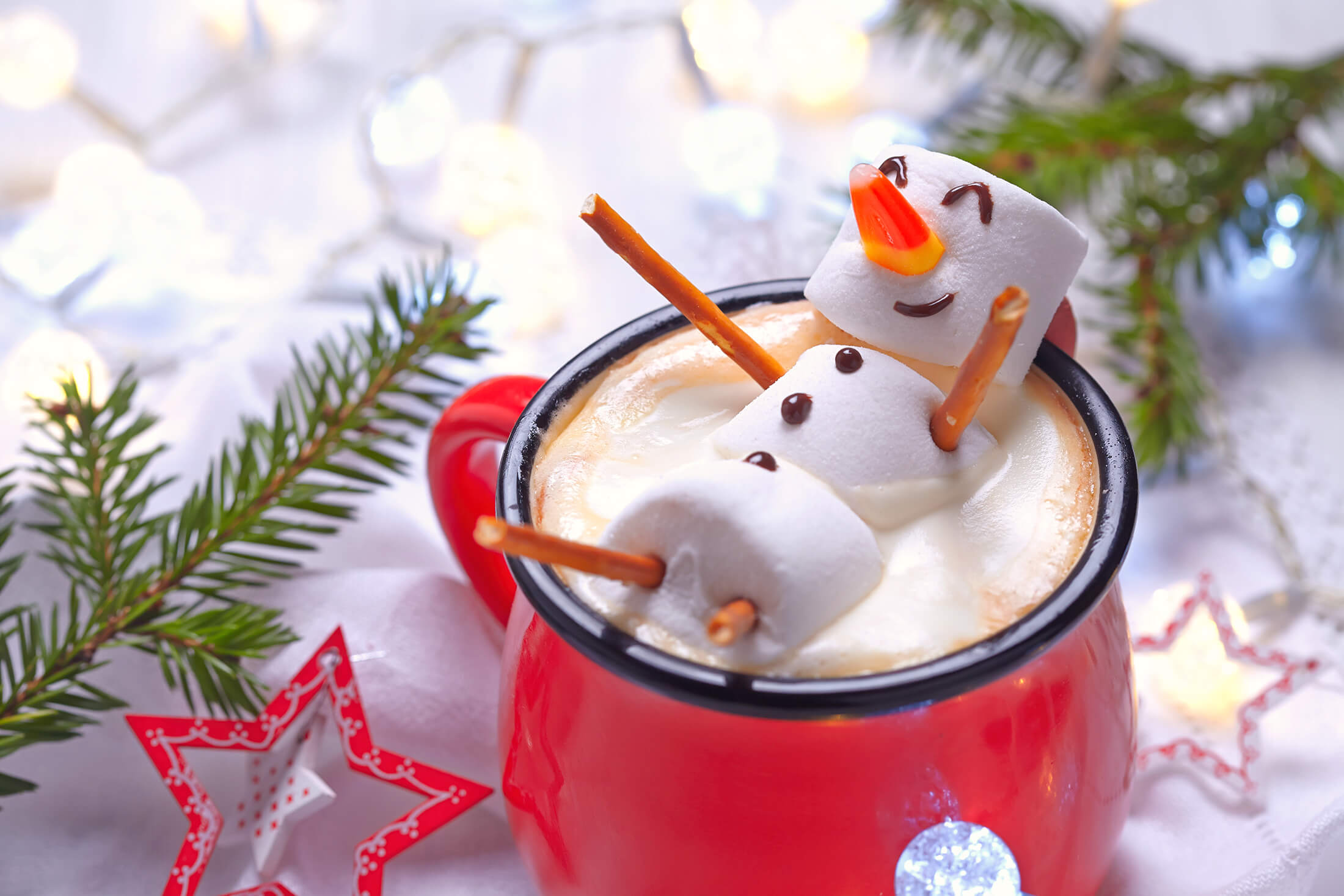 Winter marshmallow snowman smilling in cup of cocoa