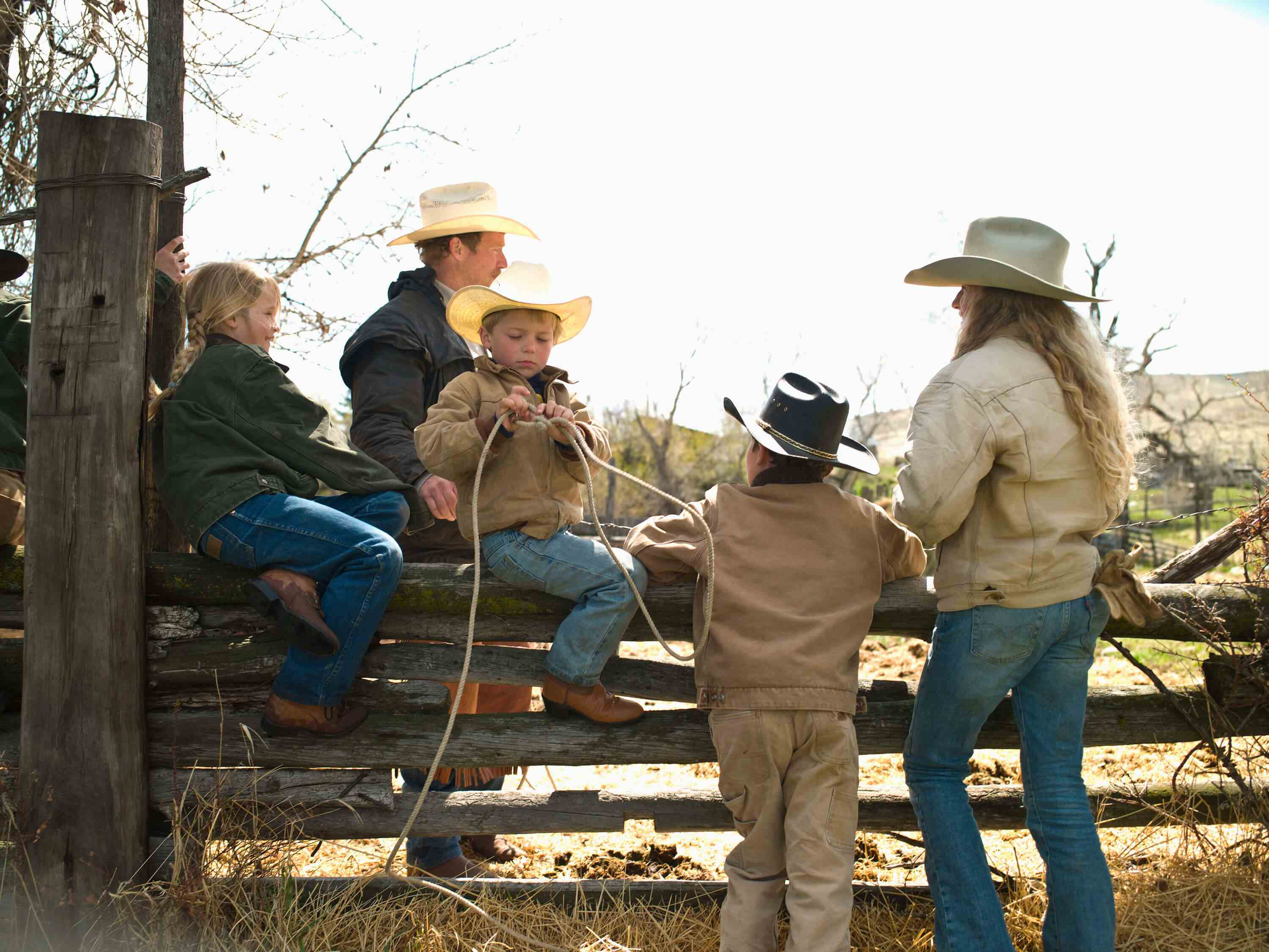Man with woman and children with cowboy hats and a rope near fence