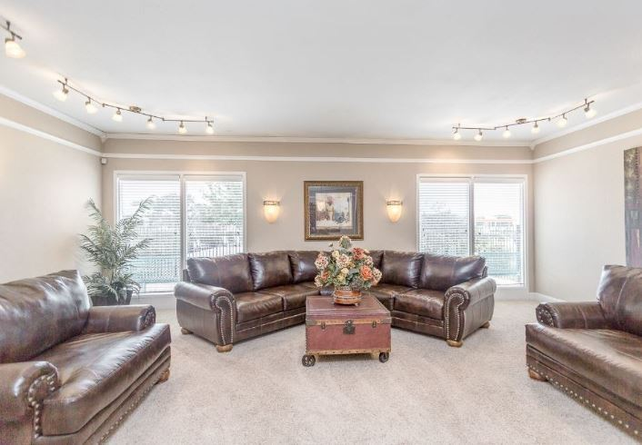 View of Brookwood Apartment Complex Office with three leather sofas and large windows.