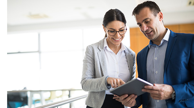 Business man and woman looking at a tablet together