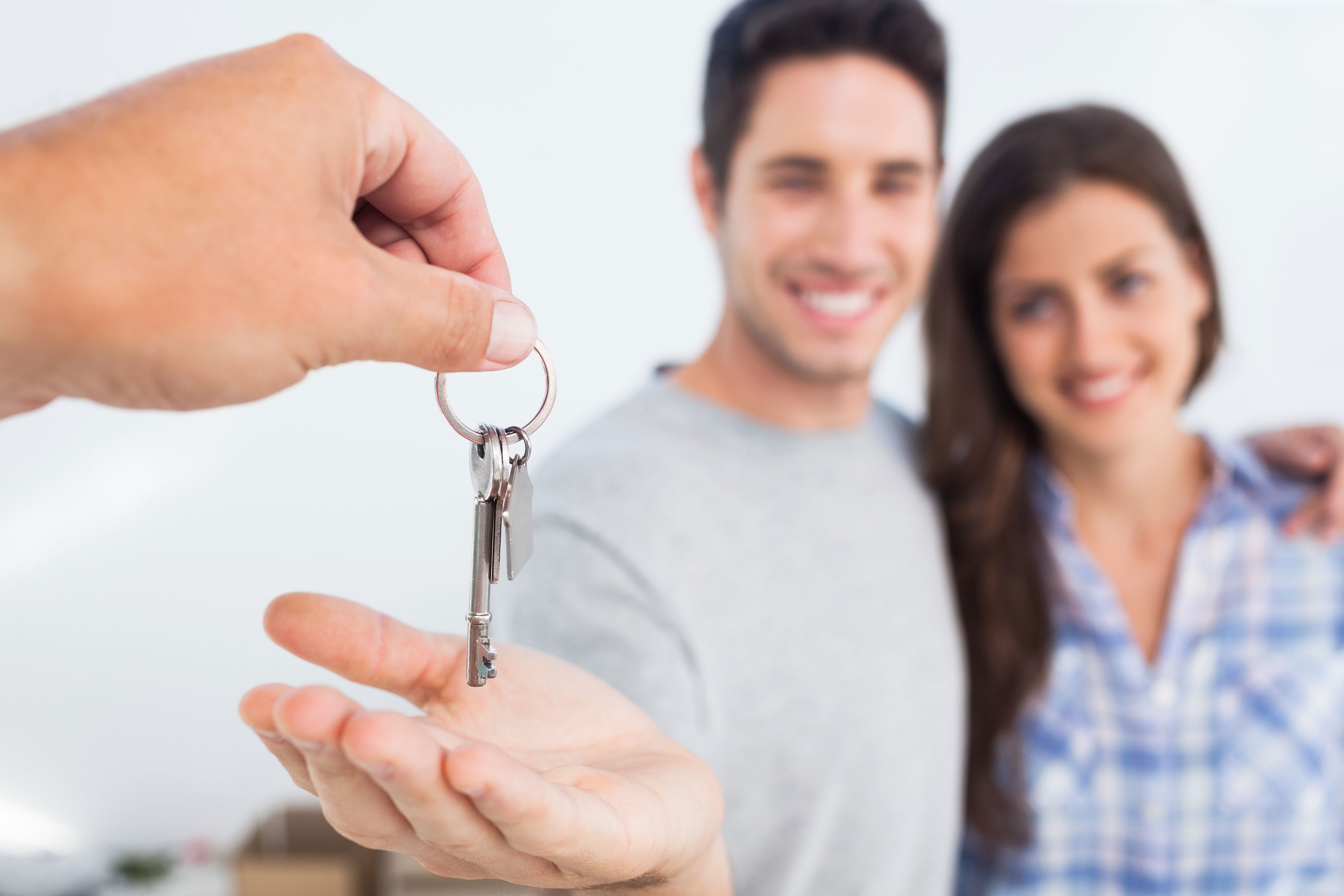 Person handing keys to man and woman blurred