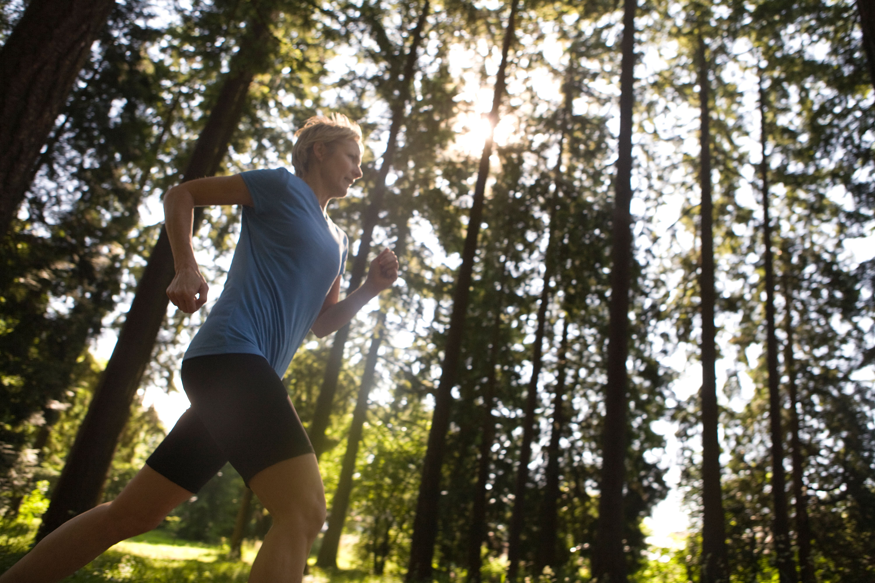 View upwards of a woman running with tall trees in the background