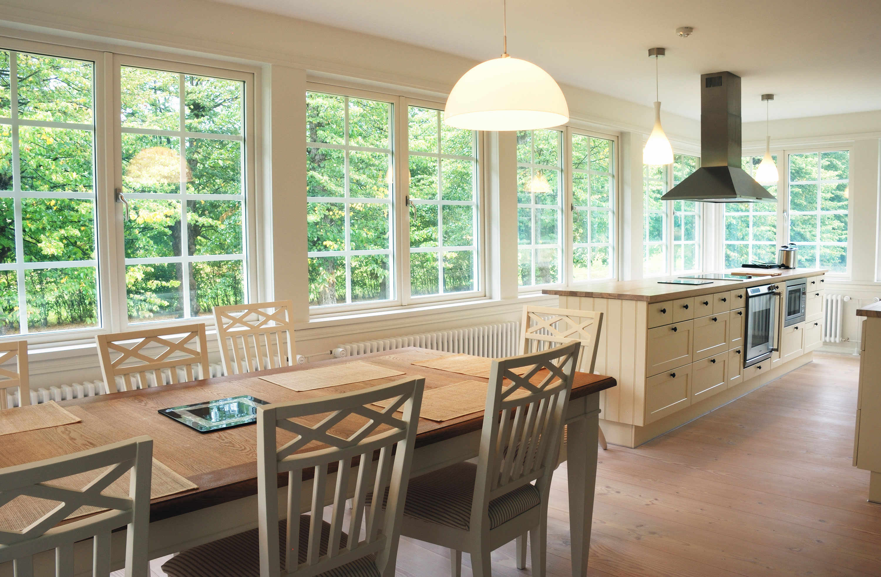 Interior of kitchen and dining with tan and white looking at multiple French windows to yard