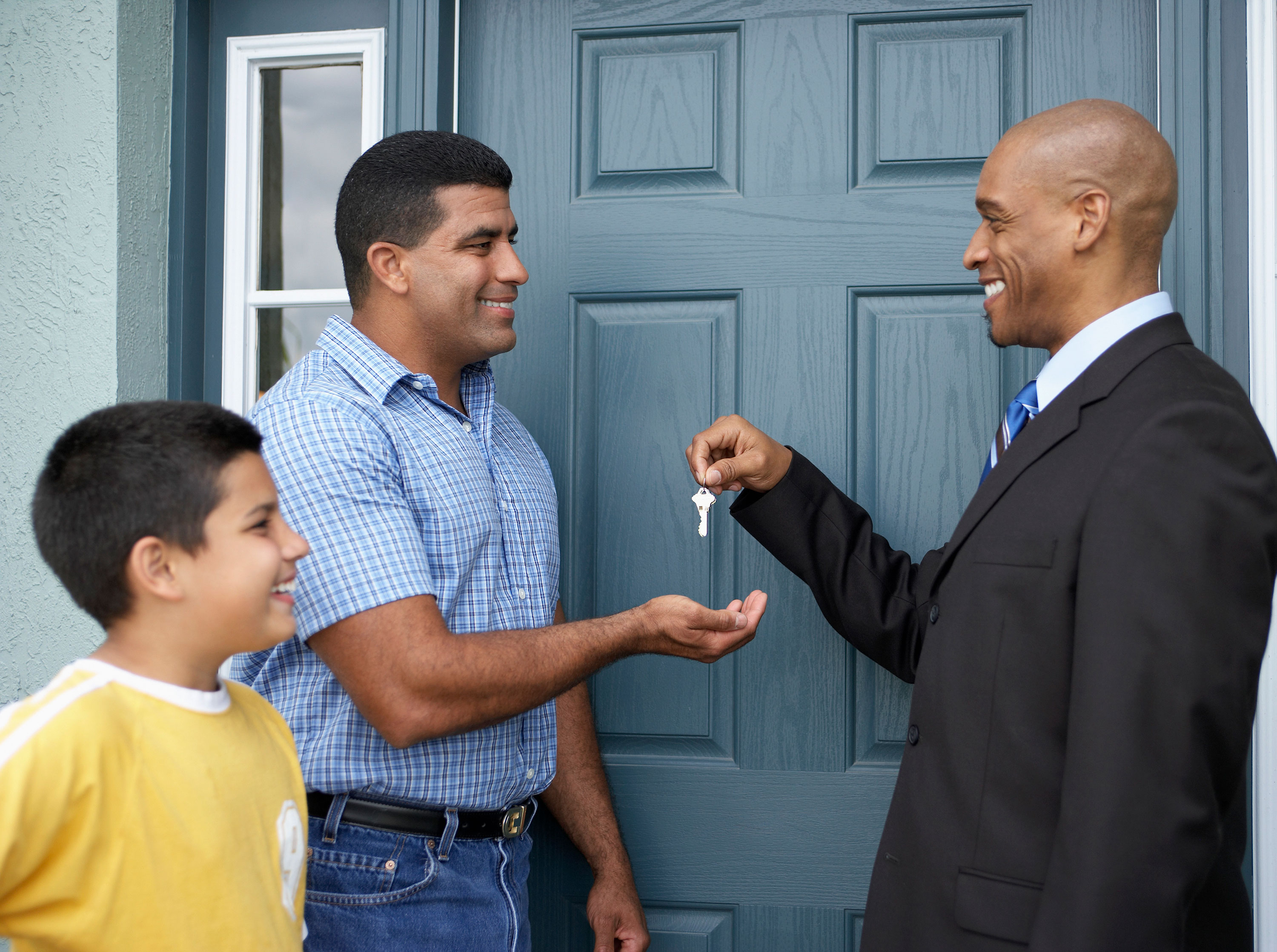 Man handing another man keys with a boy to the left in front of a blue door