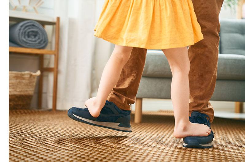 daughter standing on dads feet walking together in living room
