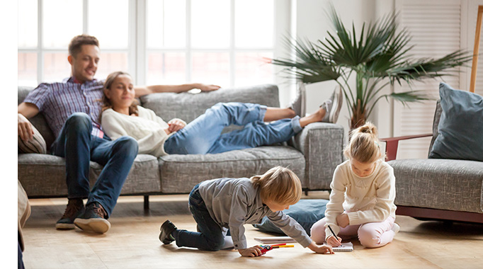 Mother and father sitting on sofa watching their children play on the floor