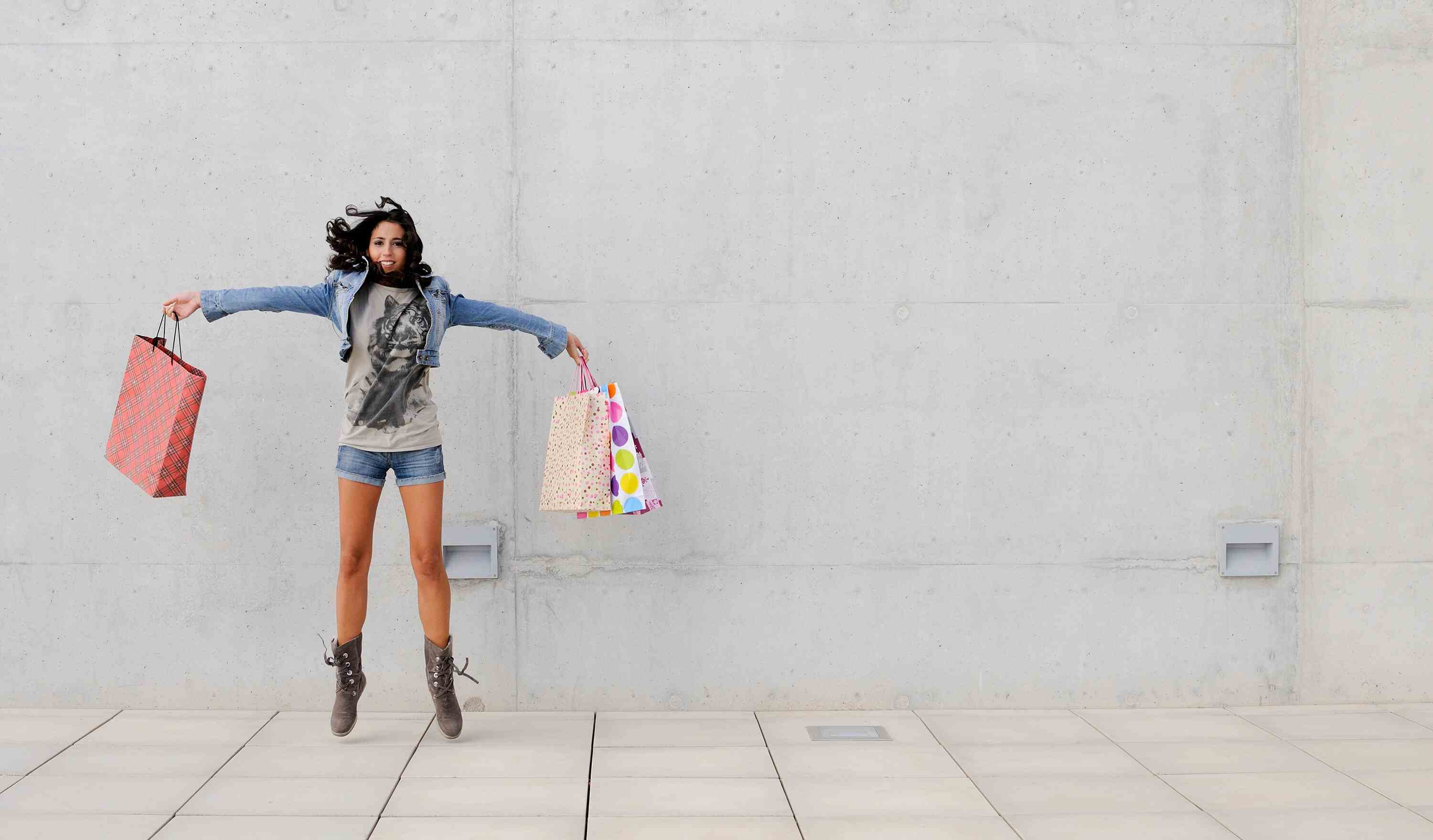 Woman jumping with shopping bags in front of cement wall