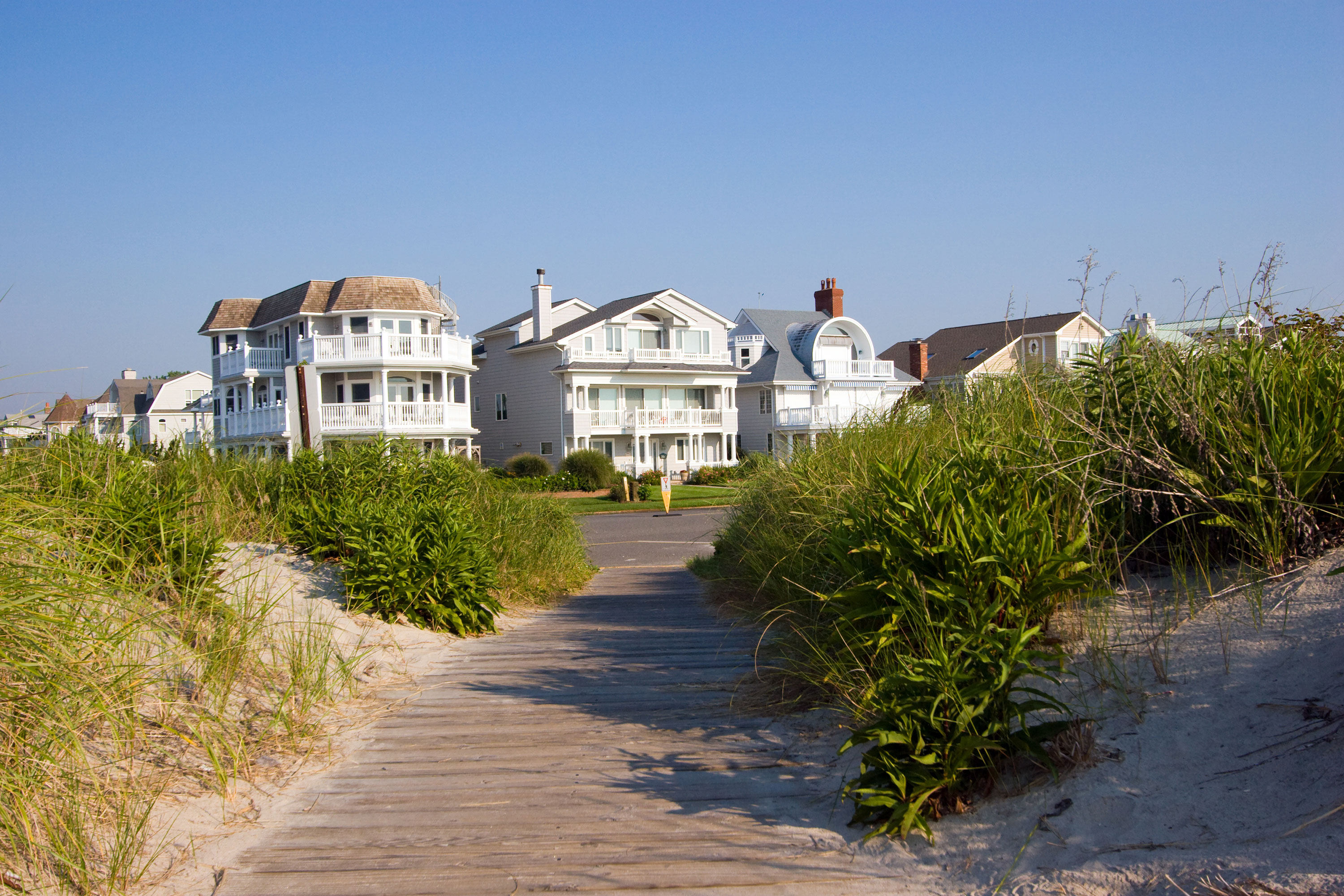 View of homes from wood path from sand with grass