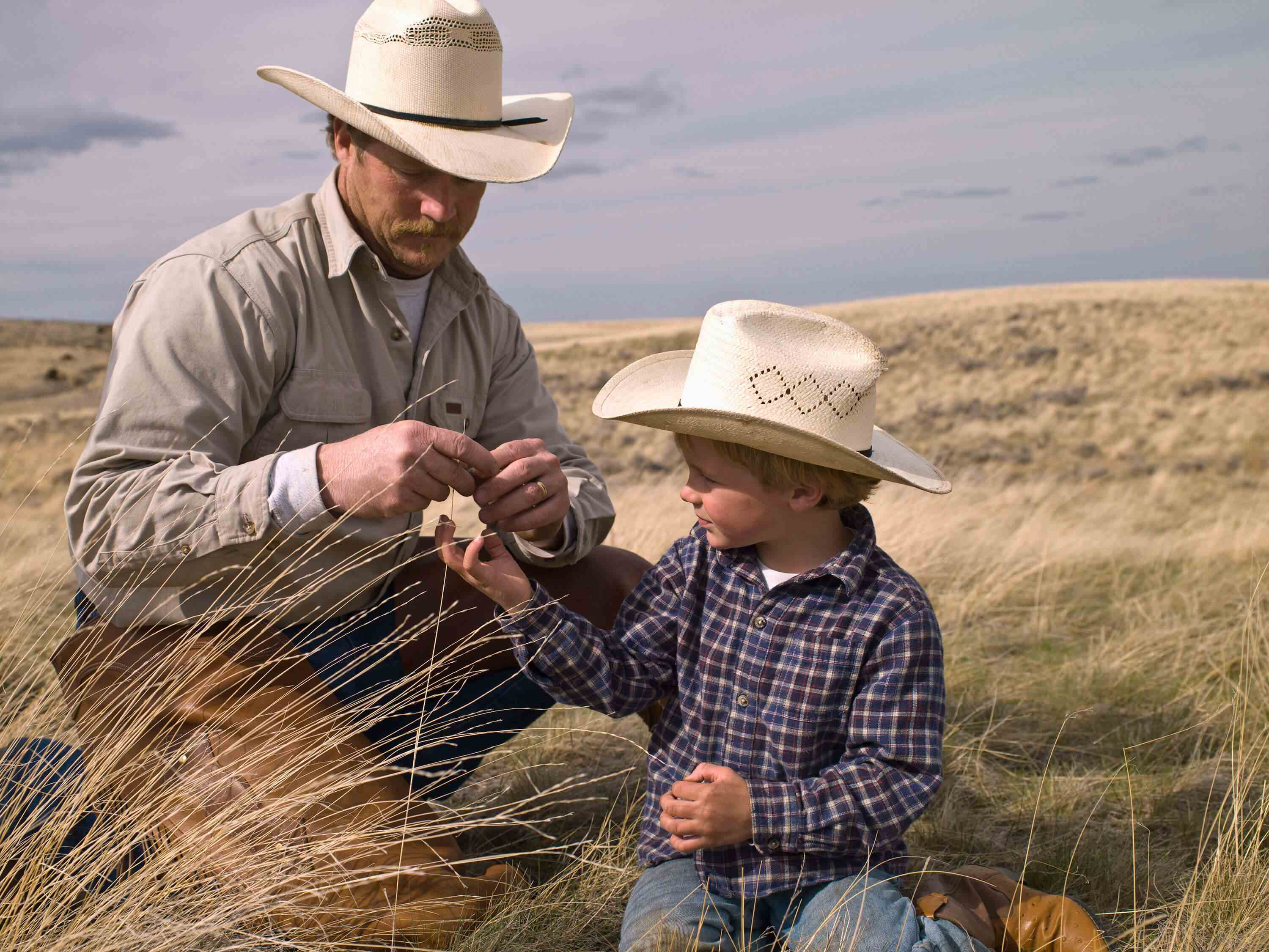 Man and boy with cowboy hats sitting in field