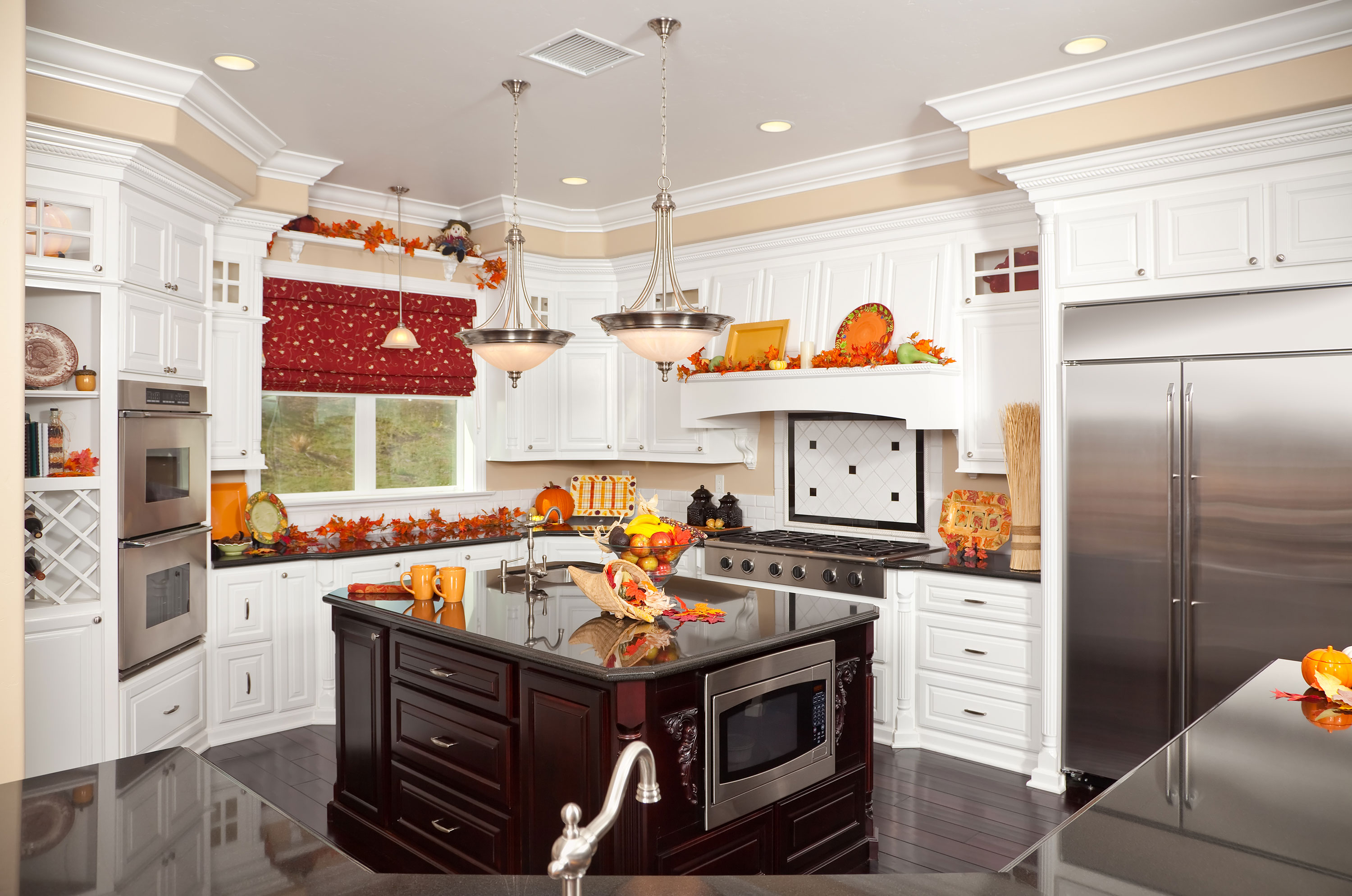 Kitchen decorated in seasonal orange and yellow for fall with dark wood island and red shade