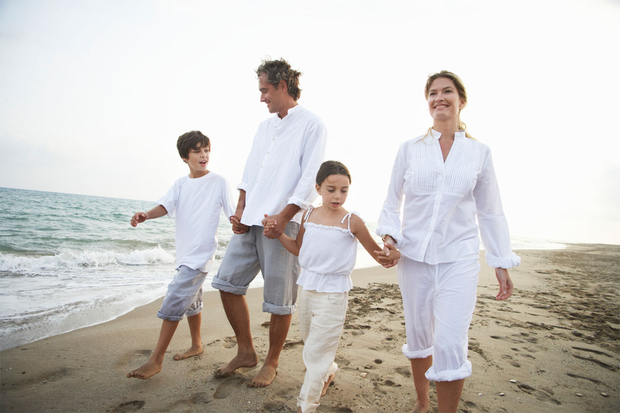 A mother and father walking their son and daughter along the beach, all dressed in white shirts and khaki pants