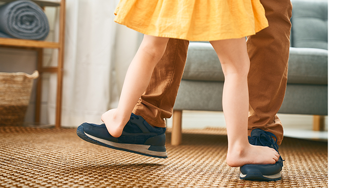 girl standing on dads feet close up yellow dress