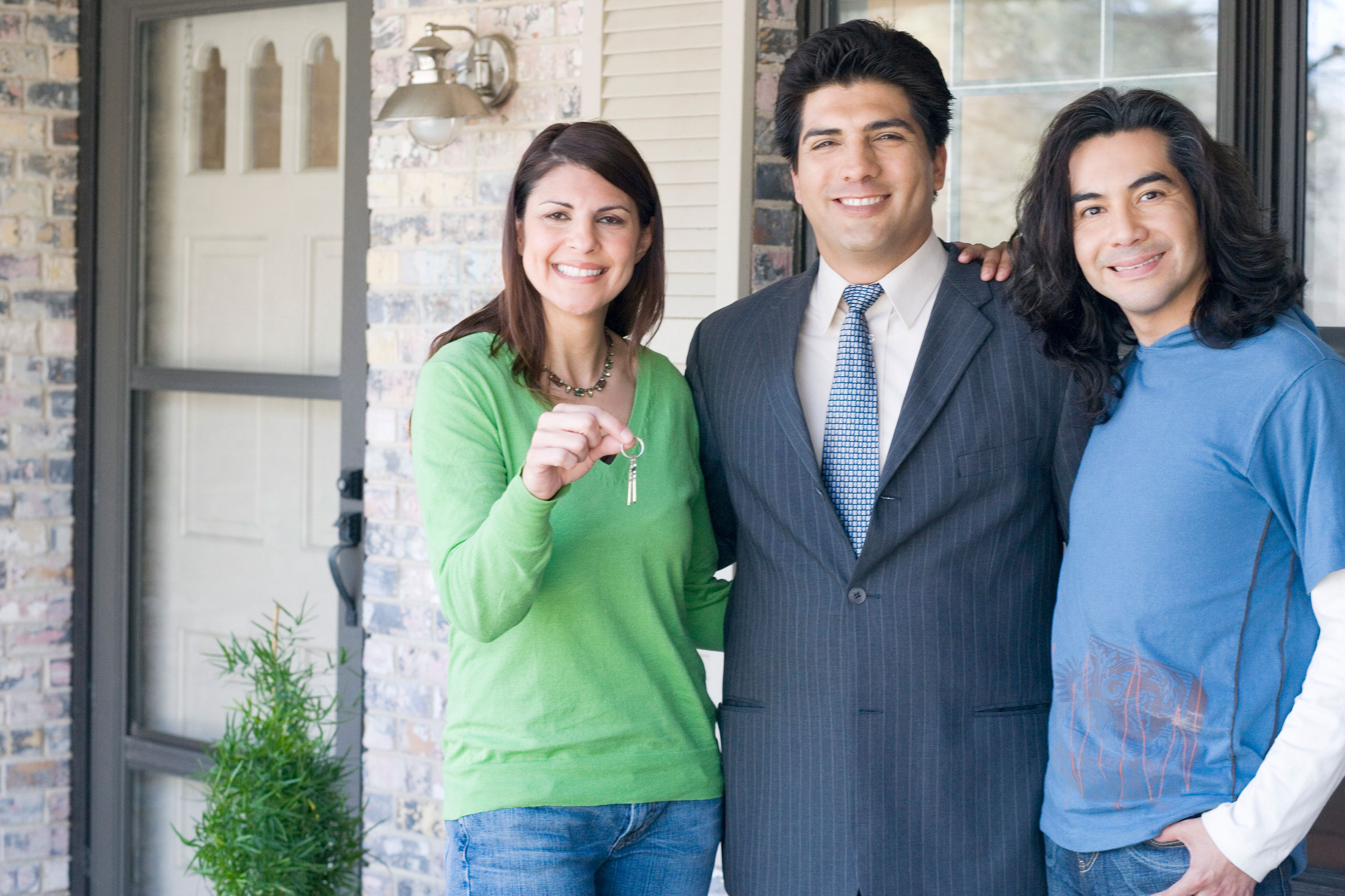 Three people standing near front door of home and woman with green sweater holding keys