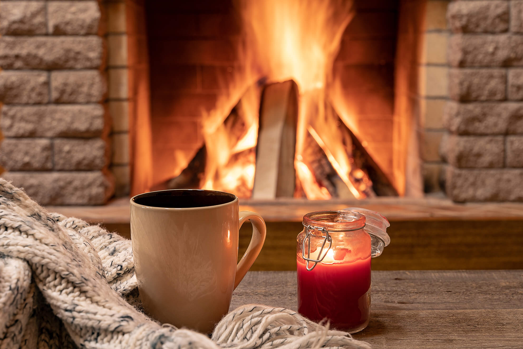 Holiday Fall coffee and candle in front of lit fireplace