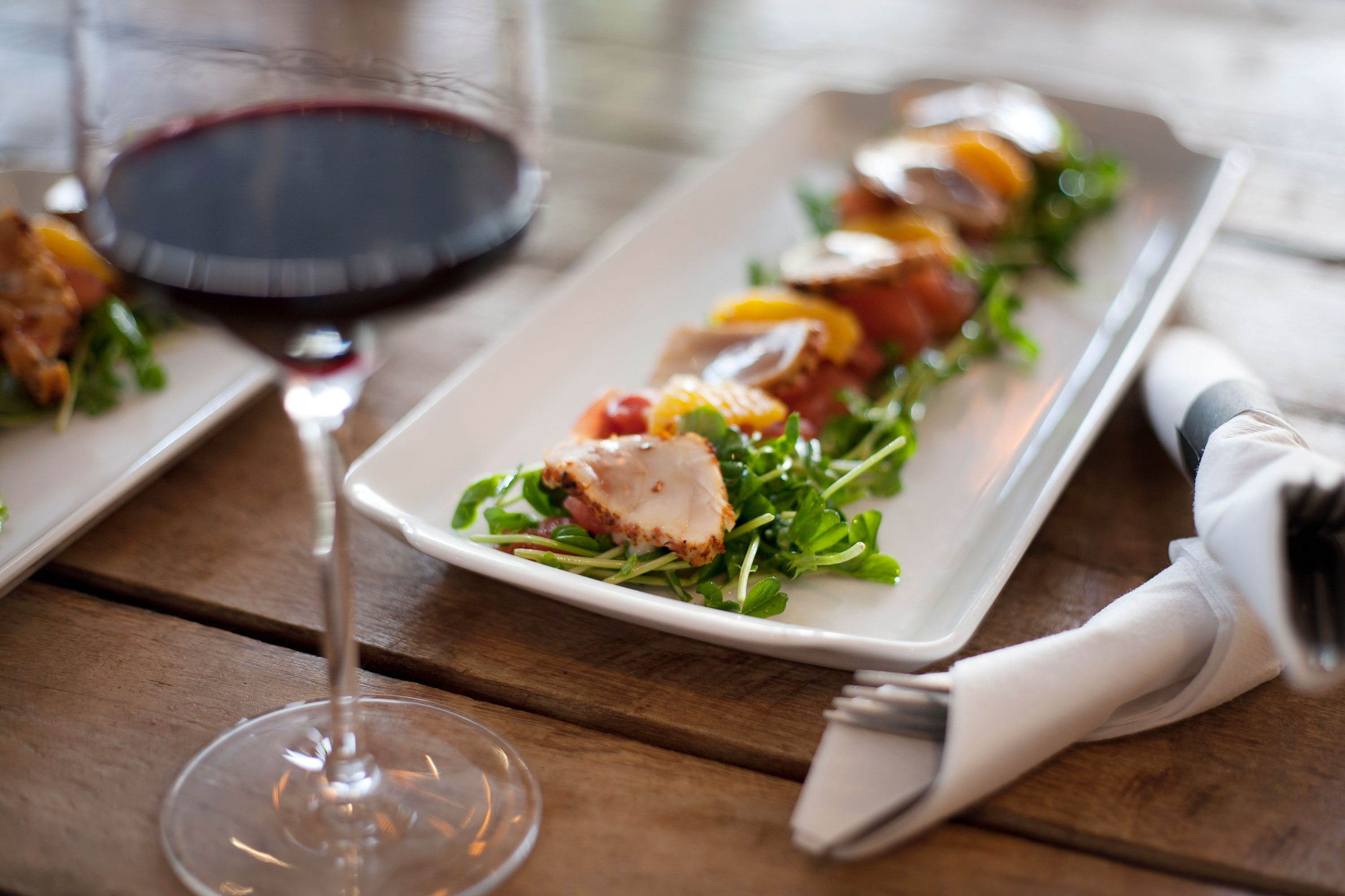 Appetizer on small rectangle plat with blurred glass of red wine on wood table