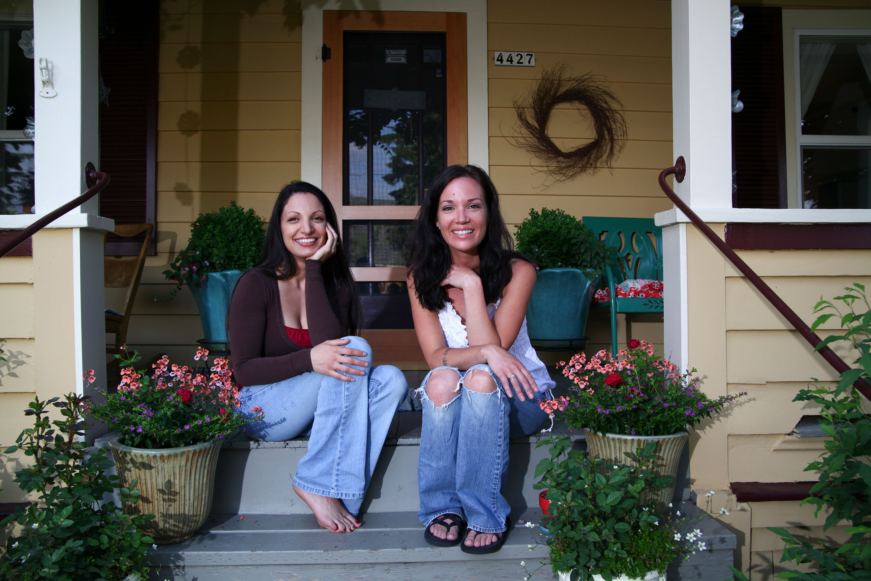 Two women sitting on step of covered gold and white with brown porch